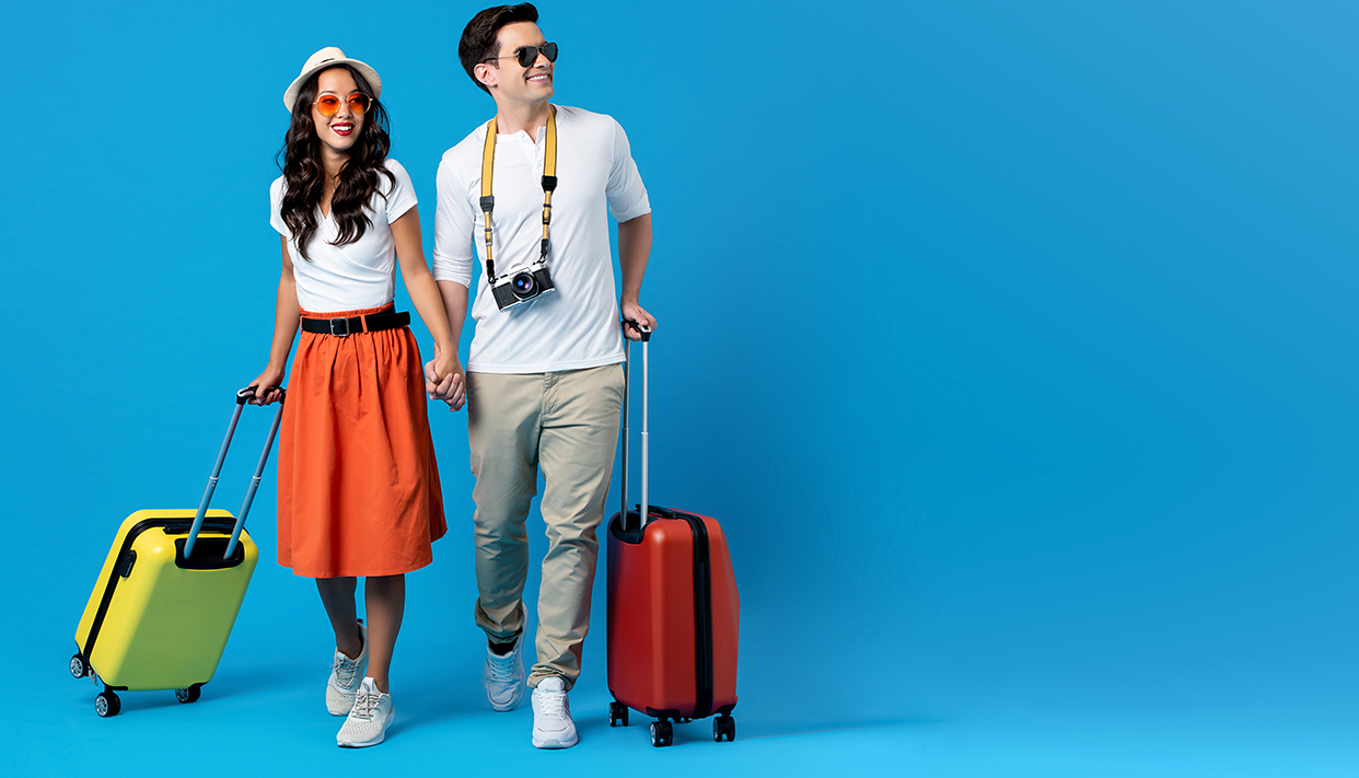 Young couple going for holidays with colorful suitcases