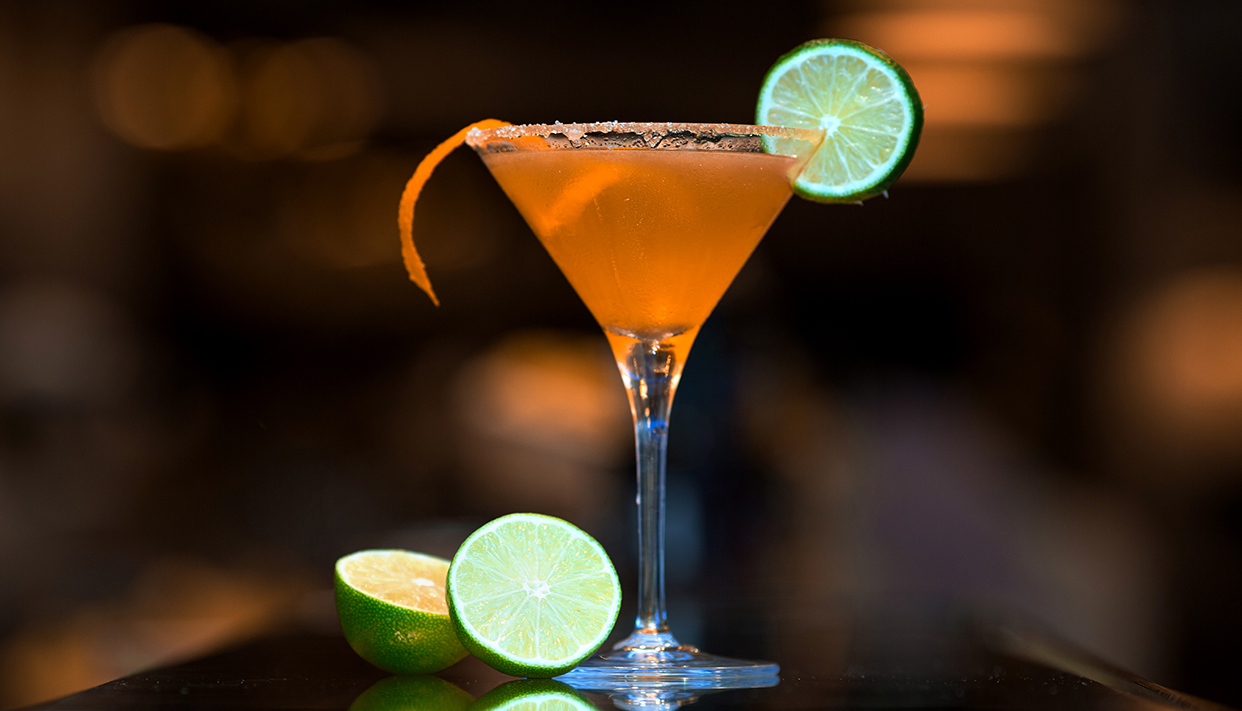 orange cocktail topped with lime slice