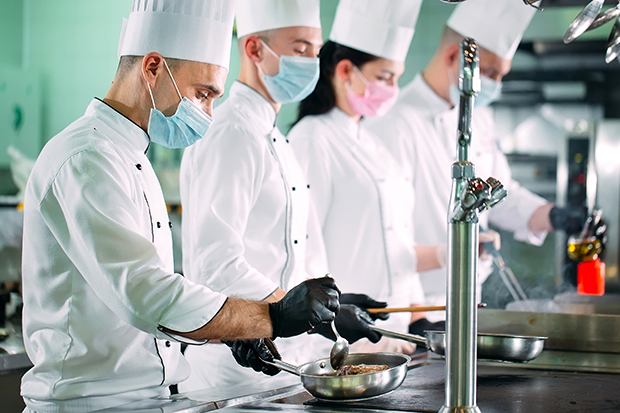 Chefs in protective masks and gloves prepare food in the kitchen