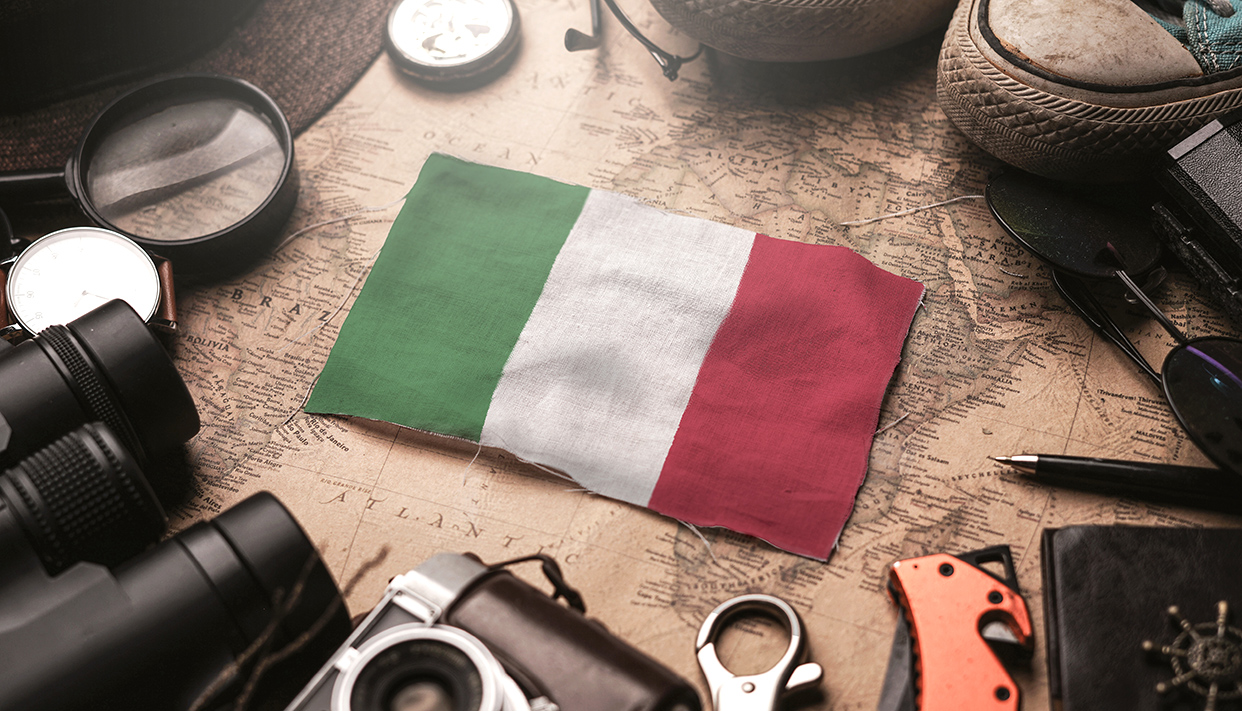 Italy Flag Between Traveler's Accessories on Old Vintage Map. Tourist Destination Concept.