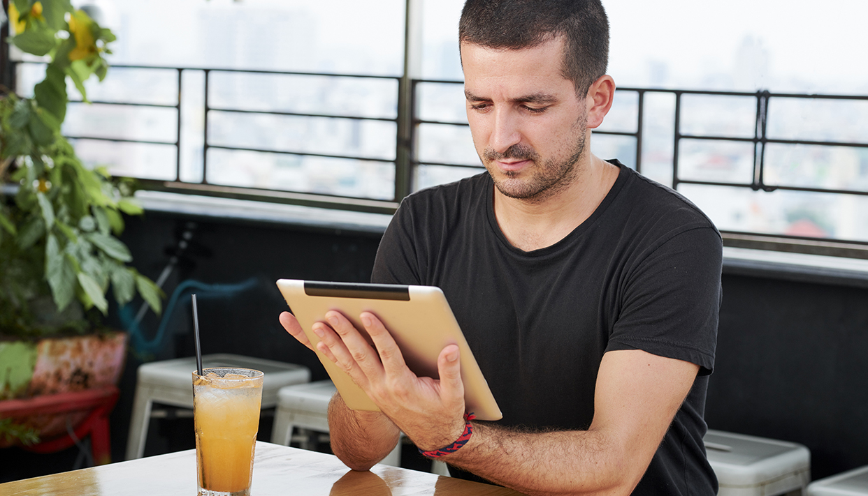 Man using tablet pc in cafe