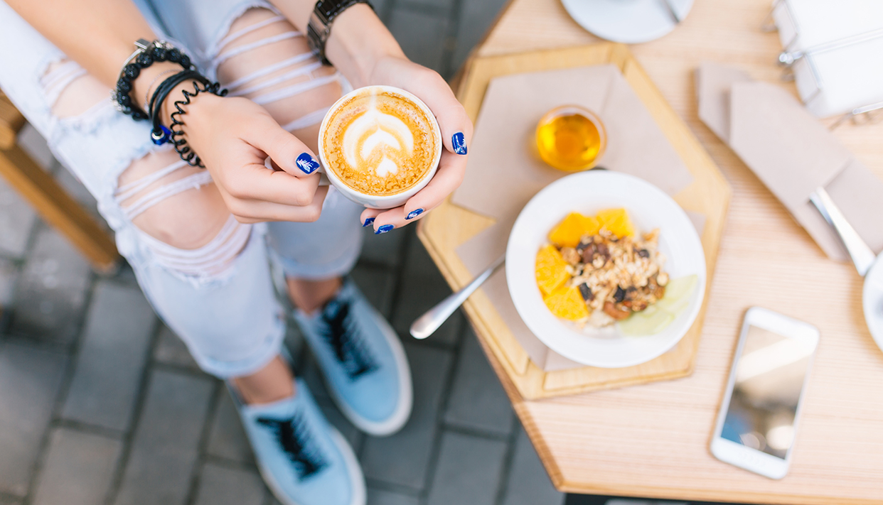 A cup of coffee with drawing in hands of young girl sitting outdoor. She wears jeans, blue sneakers, blue nails. View from above