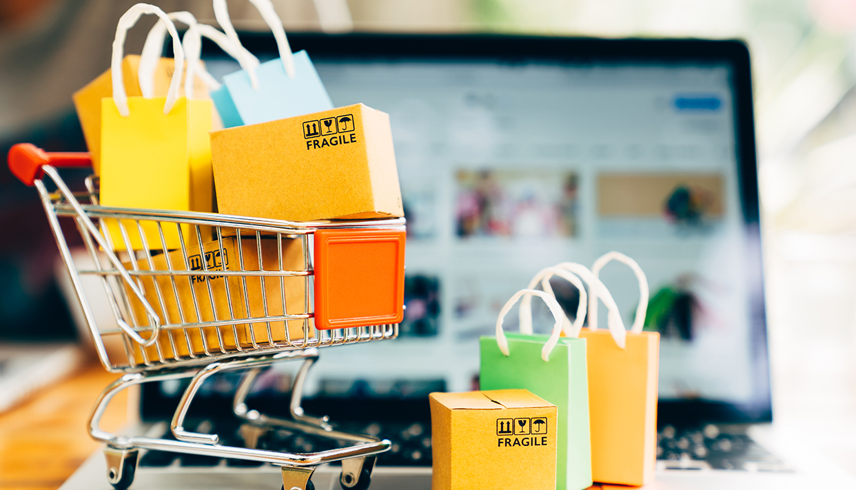Product package boxes and shopping bag in cart with laptop compu