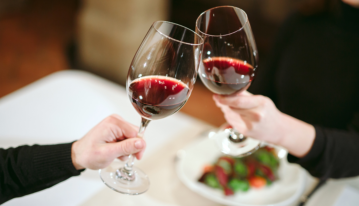 Man and woman drinking red wine. In the picture, close-up hands