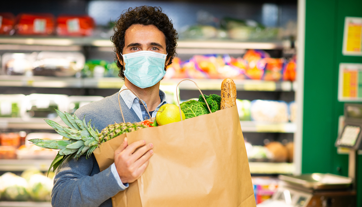 Masked man holding an healthy food bag in supermarket during the coronavirus pandemic