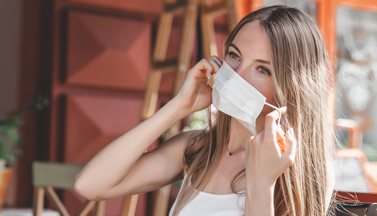 Close up portrait of a caucasian blonde girl taking off a medical mask and sitting in a city cafe on the street