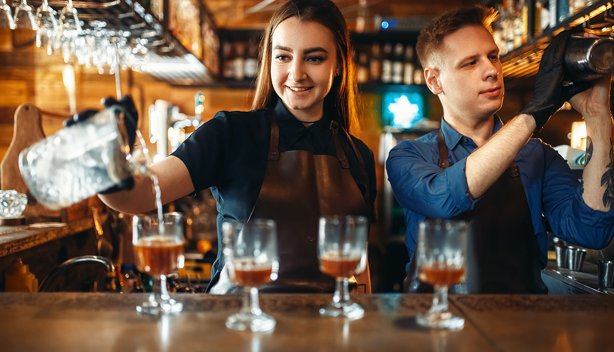 Male and female bartender at the bar counter