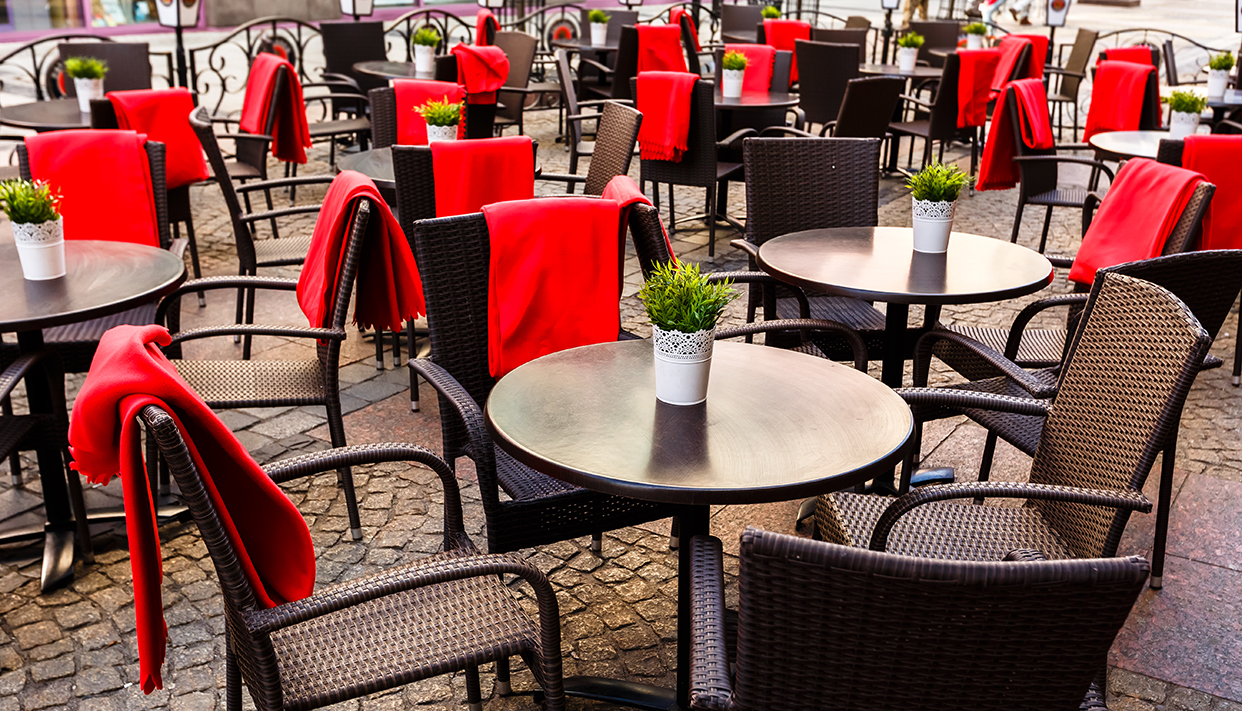 Empty tables and wicker chairs on paving stones in a cafe in  ol