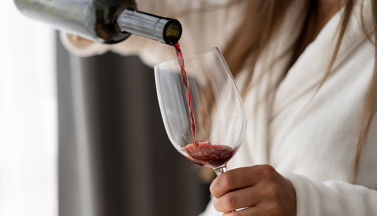 Close up of a bottle in female hands. Pour red wine into a glass. Woman in a hotel room.
