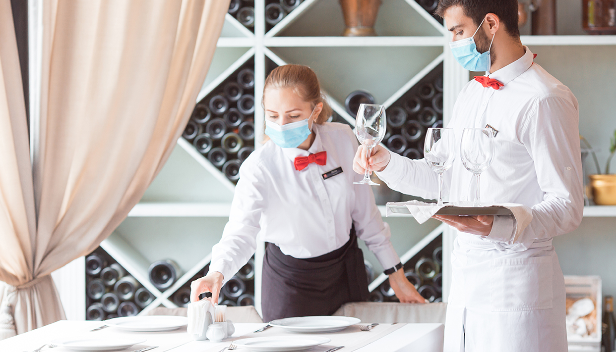 the waiter serves a table in a cafe in a protective mask.
