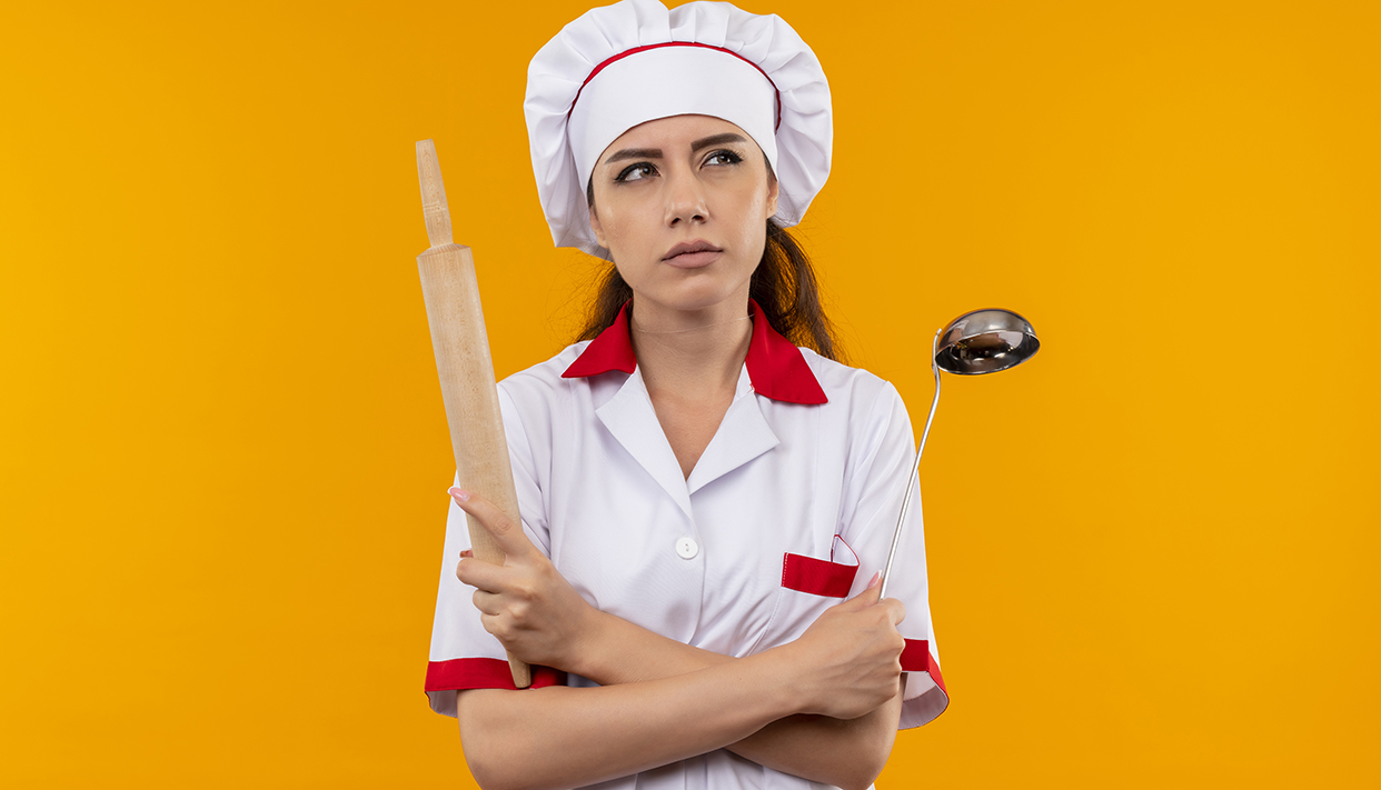 young confused caucasian cook girl in chef uniform holds rolling pin and ladle isolated on orange background with copy space