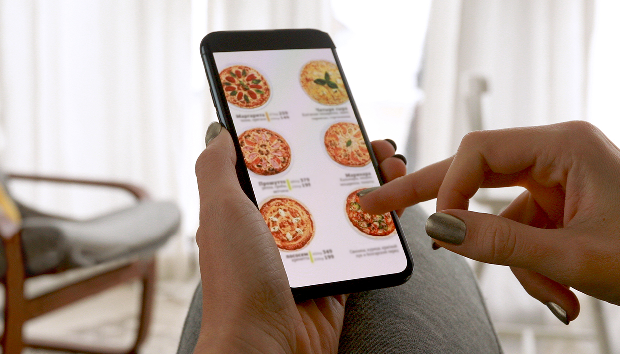 Woman ordering pizza at home online