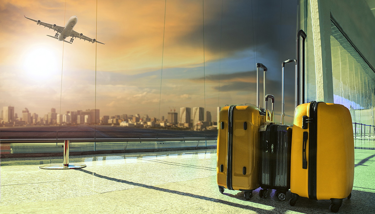traveling luggage in airport terminal building with passenger plane flying over runway