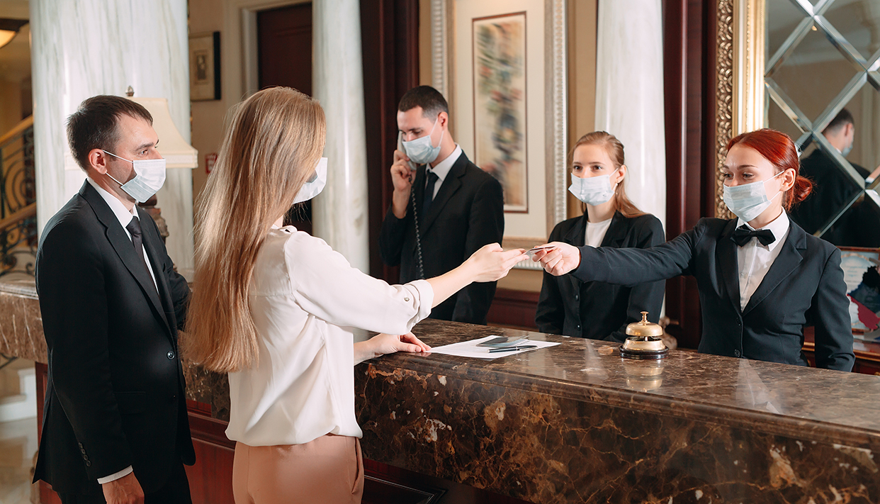 Check in hotel. receptionist at counter in hotel wearing medical
