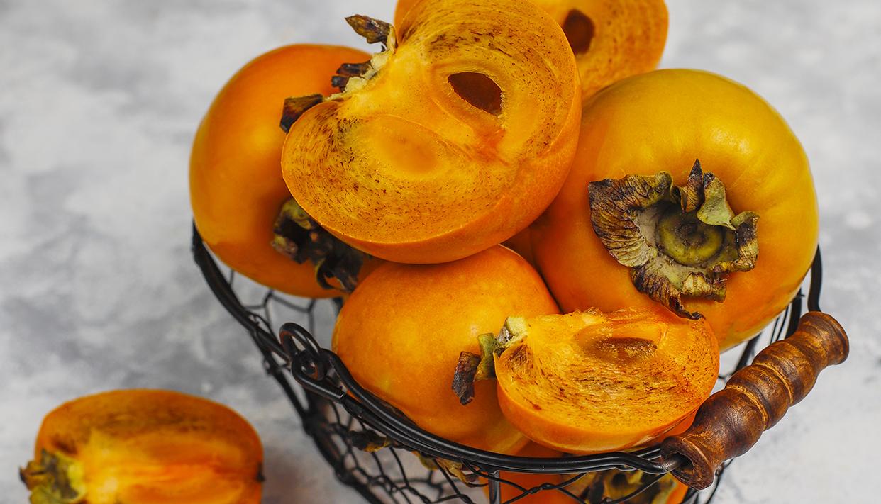 Delicious ripe persimmon fruit on concrete background