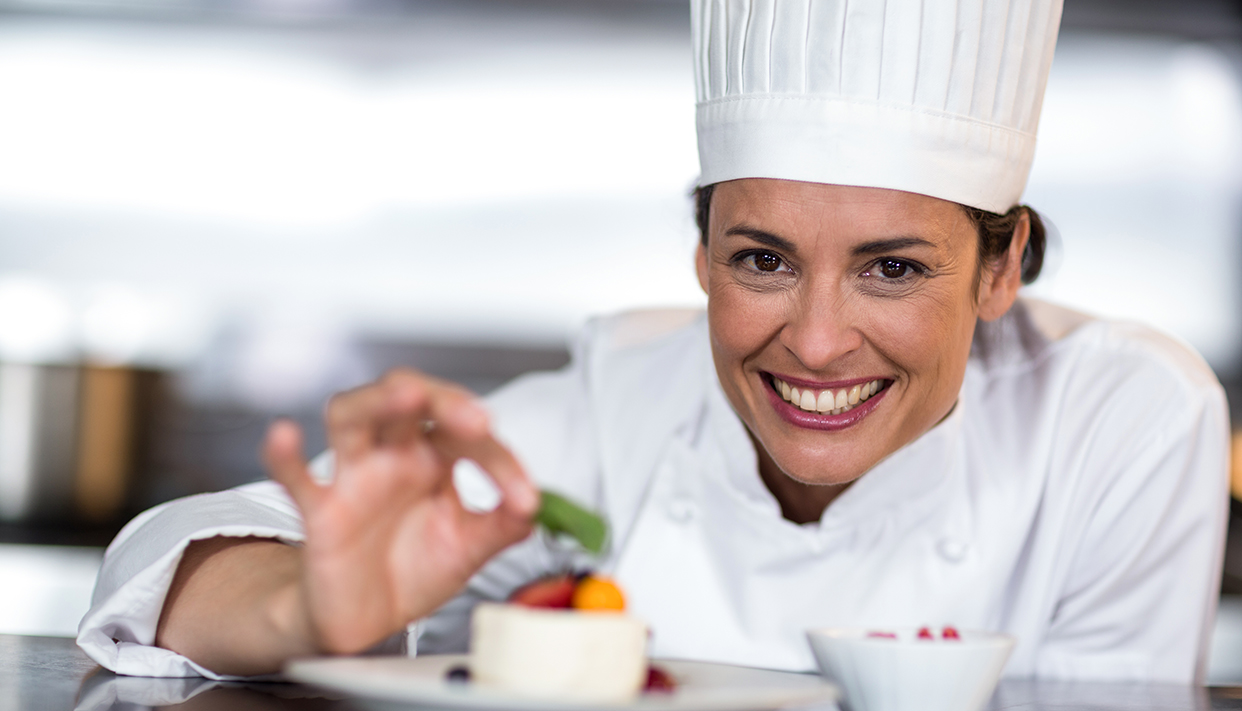 Portrait of happy female chef garnishing on food in commercial kitchen