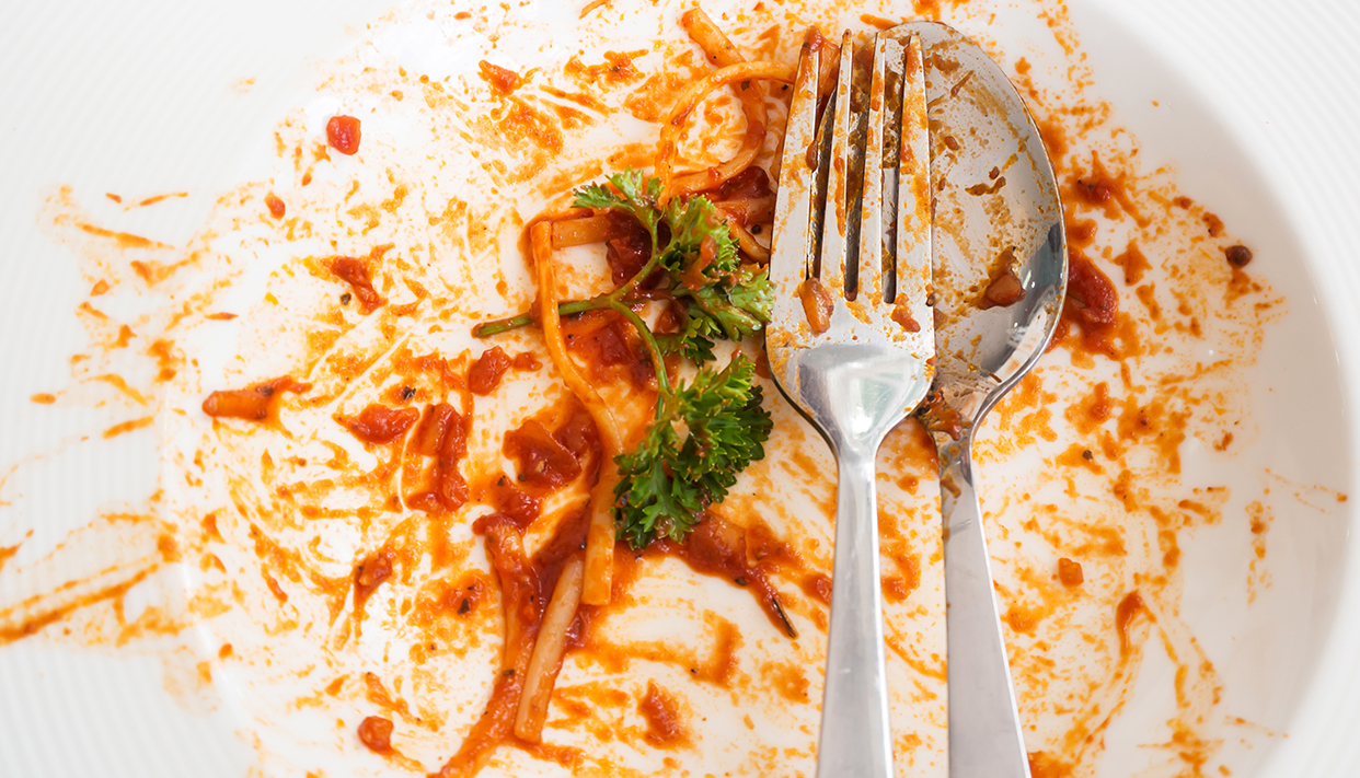 Dirty white plate. After meal of spaghetti red sauce. Top view.
