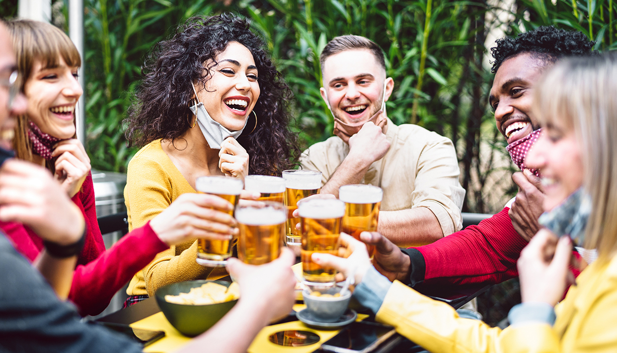 Young people toasting beer wearing open face mask – New normal l
