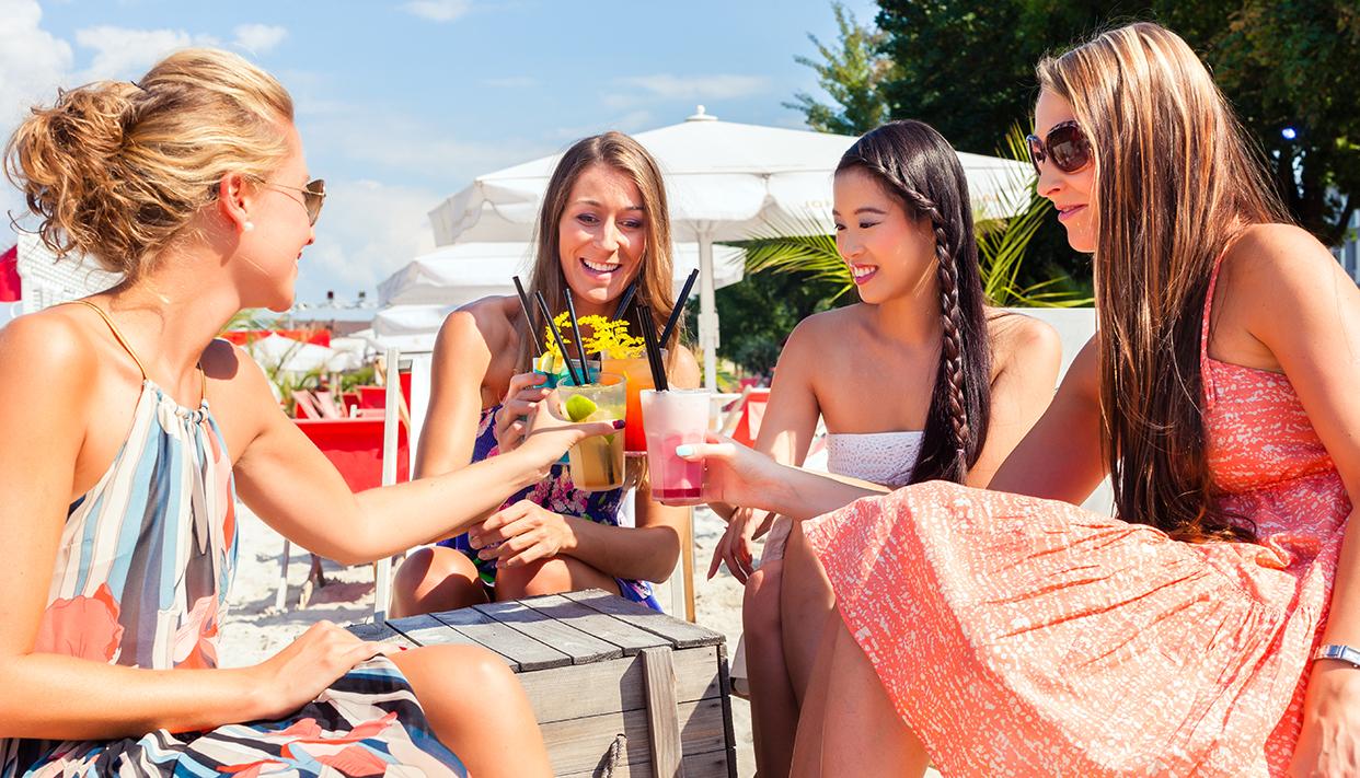 Friends drinking cocktails in beach bar