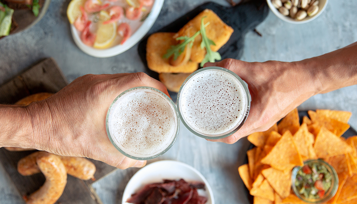 Top view of beer glasses with foam on top and delicious snacks