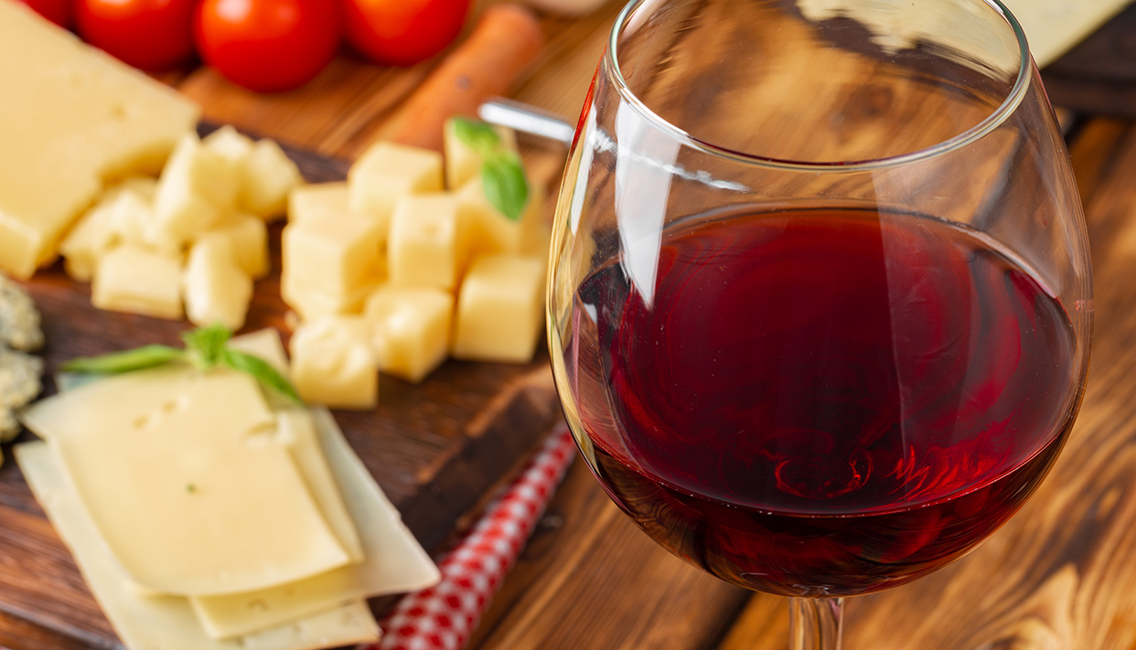 Red wine glass and cheese blocks on wooden table