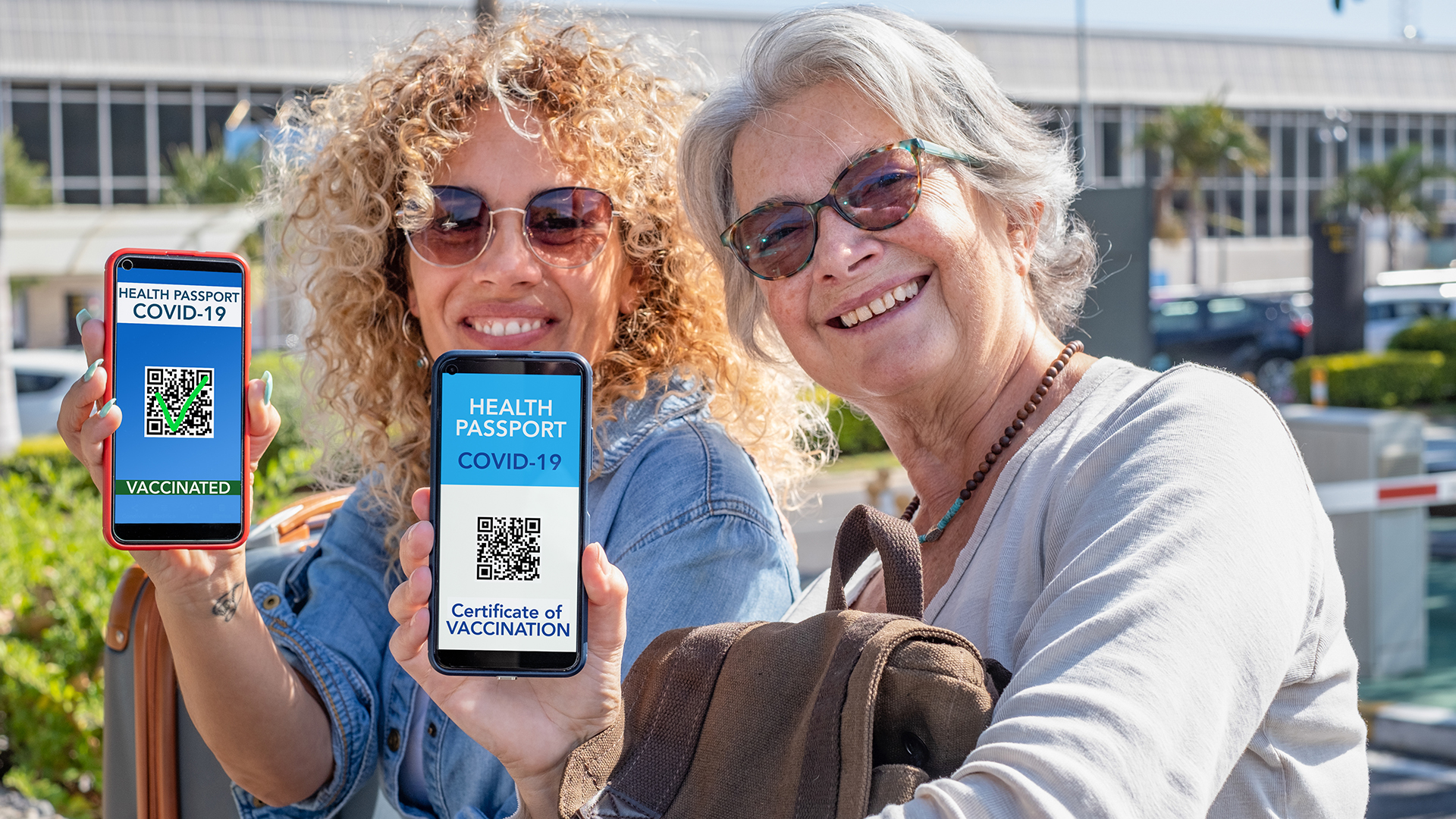 Two smiling women ready to travel showing digital health certifi