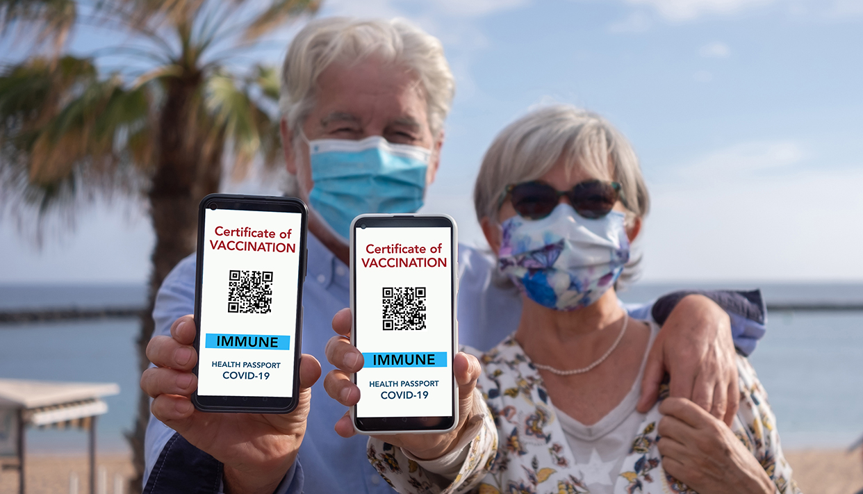 Senior couple shows digital health passport app for people vacci