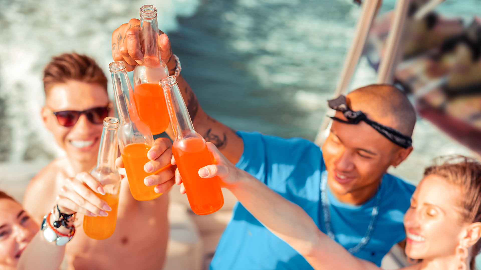 High-spirited people drinking soft drinks on a yacht