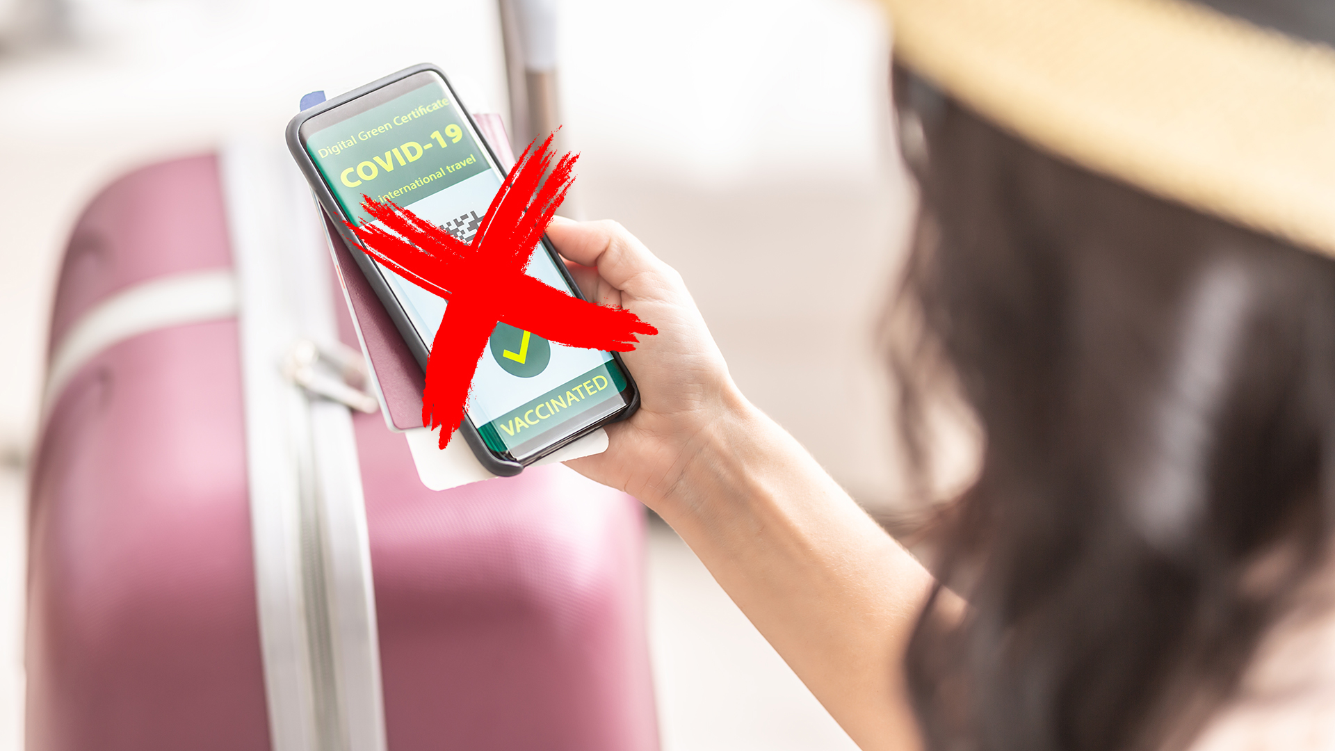 Digital green certificate for international travel displays green Covid-19 vaccinated tick and a QR code in the smartphone of a woman.